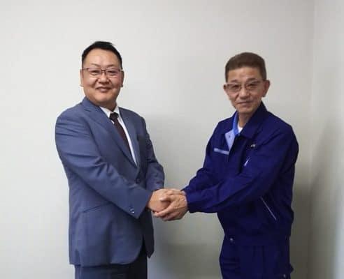 がっちり握手する社長と組合長